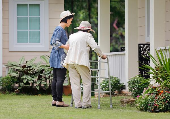 A nurse helps a woman outside and adult family home